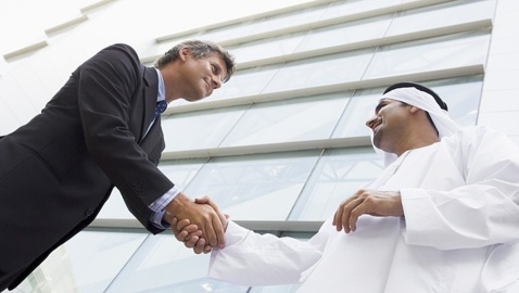 Two businessmen outdoors by building shaking hands and smiling high key/selective focus
